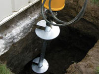 Installing a helical pier system in the earth around a foundation in Florissant
